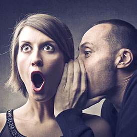 Man telling secret to woman about lice infestation